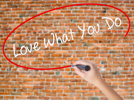Woman Hand Writing Love What You Do with black marker on visual screen. Isolated on bricks. Business concept. Stock Photo