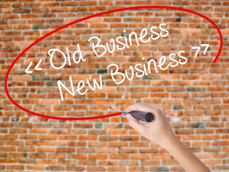 Woman Hand Writing Old Business - New Business with black marker on visual screen. Isolated on bricks. Business concept. Stock Photo Stock Photo