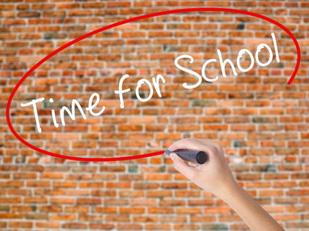 Woman Hand Writing Time for School with black marker on visual screen. Isolated on bricks. Business concept. Stock Photo Stock Photo