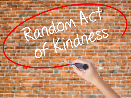 Woman Hand Writing Random Act of Kindness with black marker on visual screen. Isolated on bricks. Business concept. Stock Photo