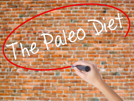 Woman Hand Writing The Paleo Diet with black marker on visual screen. Isolated on bricks. Medical, technology, internet concept. Stock Image