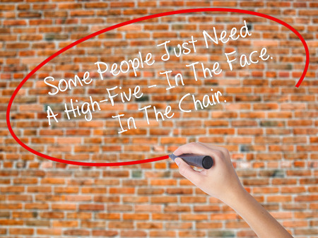 stupidity: Woman Hand Writing Some People Just Need A High-Five - In The Face. In The Chair  with black marker on visual screen. Isolated on bricks. Business, technology, internet concept. Stock Photo
