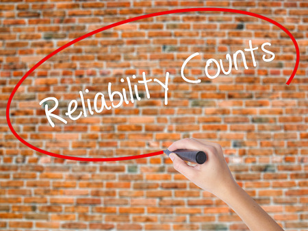 Woman Hand Writing Reliability Counts with black marker on visual screen. Isolated on bricks. Business, technology, internet concept.