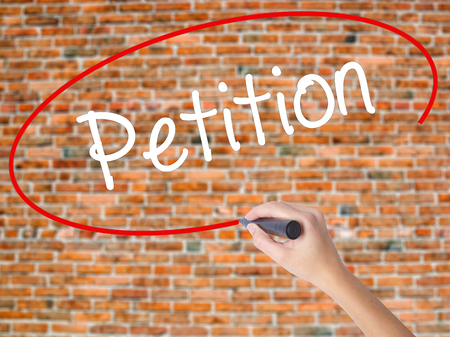 Woman Hand Writing Petition with black marker on visual screen. Isolated on bricks. Business concept. Stock Photo