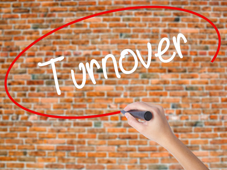 Woman Hand Writing Turnover with black marker on visual screen. Isolated on bricks. Business concept. Stock Photo