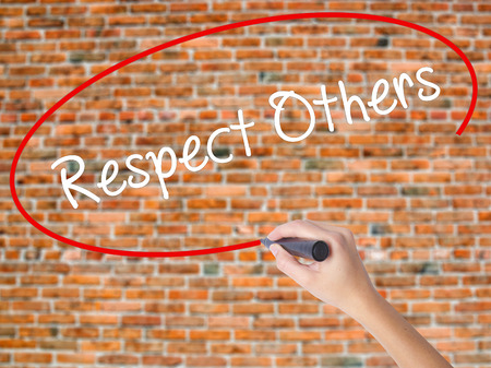 Woman Hand Writing Respect Others with black marker on visual screen. Isolated on bricks. Business concept. Stock Photo