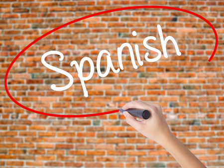 bilingual: Woman Hand Writing Spanish with black marker on visual screen. Isolated on bricks. Business concept. Stock Photo