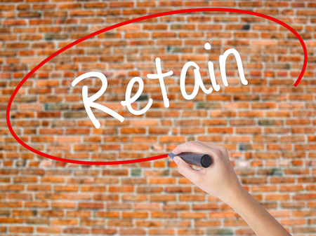 retained: Woman Hand Writing Retain with black marker on visual screen. Isolated on bricks. Business concept. Stock Photo