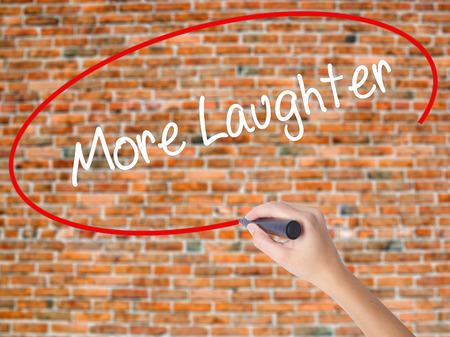 Woman Hand Writing More Laughter with black marker on visual screen. Isolated on bricks. Business concept. Stock Photo