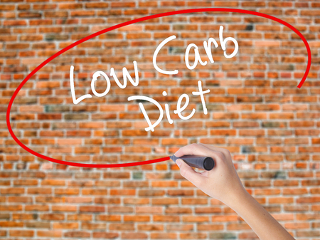 Woman Hand Writing Low Carb Diet with black marker on visual screen. Isolated on bricks. Business concept. Stock Photo Stock Photo
