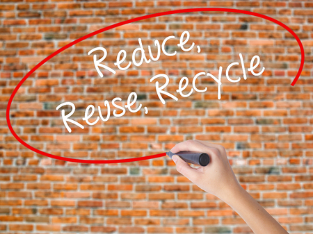 reduce reutiliza recicla: Woman Hand Writing Reduce Reuse Recycle with black marker on visual screen. Isolated on bricks. Business concept. Stock Photo
