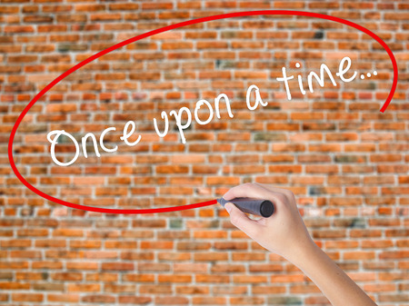 phrase novel: Woman Hand Writing Once upon a time... with black marker on visual screen. Isolated on bricks. Business concept. Stock Photo