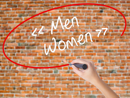 challenging sex: Woman Hand Writing Men - Women with black marker on visual screen. Isolated on bricks. Business concept. Stock Photo