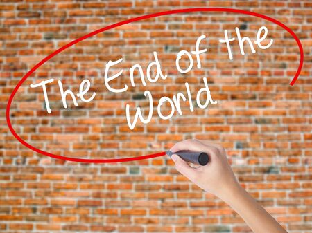 Woman Hand Writing The End of the World with black marker on visual screen. Isolated on bricks. Business concept. Stock Photo