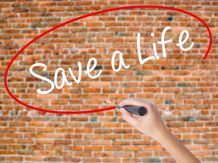t bar: Woman Hand Writing Save a Life  with black marker on visual screen. Isolated on bricks. Business concept. Stock Photo