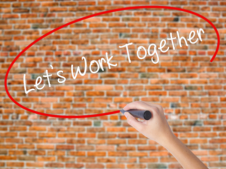 combined effort: Woman Hand Writing Lets Work Together with black marker on visual screen. Isolated on bricks. Business concept. Stock Photo