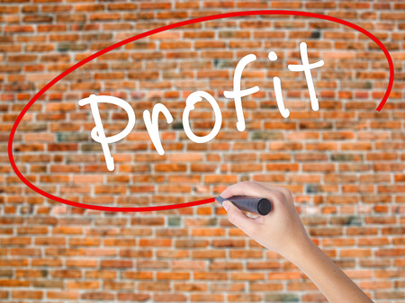 Woman Hand Writing Profit with black marker on visual screen. Isolated on bricks. Business concept. Stock Photo Stock Photo