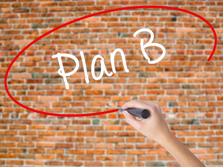 Woman Hand Writing Plan B with black marker on visual screen. Isolated on bricks. Business concept. Stock Photo Stock Photo