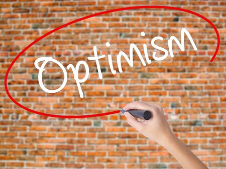 Woman Hand Writing Optimism  with black marker on visual screen. Isolated on bricks. Business concept. Stock Photo