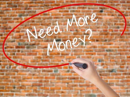Woman Hand Writing Need More Money? with black marker on visual screen. Isolated on bricks. Business concept. Stock Photo Stock Photo
