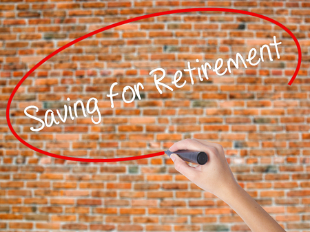 Woman Hand Writing Saving for Retirement with black marker on visual screen. Isolated on bricks. Business concept. Stock Photo Stock Photo