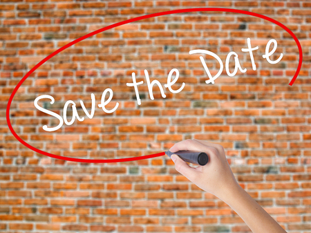 important date: Woman Hand Writing Save the Date  with black marker on visual screen. Isolated on bricks. Business concept. Stock Photo Stock Photo