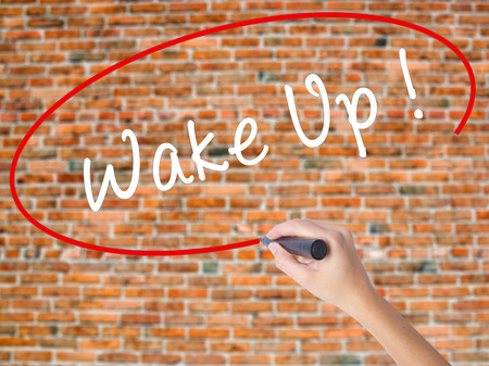 modify: Woman Hand Writing Wake Up with black marker on visual screen. Isolated on bricks. Business concept. Stock Photo