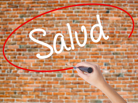 Woman Hand Writing Salud (Health in Spanish) with black marker on visual screen. Isolated on bricks. Business concept. Stock Photo