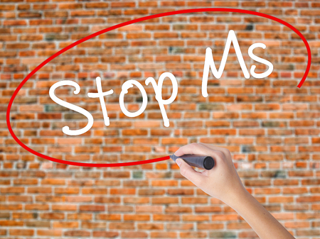 Woman Hand Writing Stop Ms with black marker on visual screen. Isolated on bricks. Business concept. Stock Photo