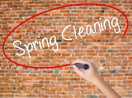 Woman Hand Writing Spring Cleaning with black marker on visual screen. Isolated on bricks. Business concept. Stock Photo