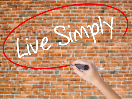 Woman Hand Writing Live Simply with black marker on visual screen. Isolated on bricks. Business concept. Stock Photo Stock Photo