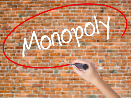 Woman Hand Writing Monopoly with black marker on visual screen. Isolated on bricks. Business concept. Stock Photo