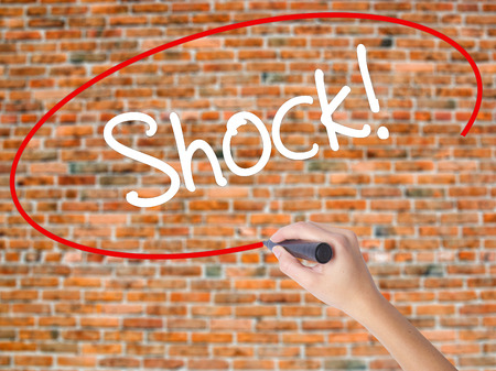 Woman Hand Writing Shock! with black marker on visual screen. Isolated on bricks. Business concept. Stock Photo Stock Photo