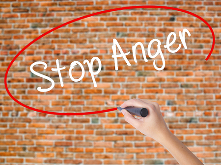 conflictos sociales: Woman Hand Writing Stop Anger with black marker on visual screen. Isolated on bricks. Business concept. Stock Photo Foto de archivo