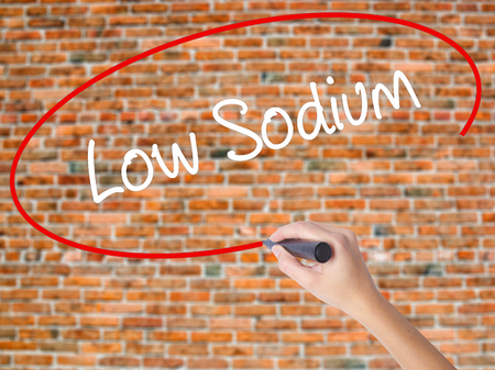 Woman Hand Writing Low Sodium with black marker on visual screen. Isolated on bricks. Business concept. Stock Photo