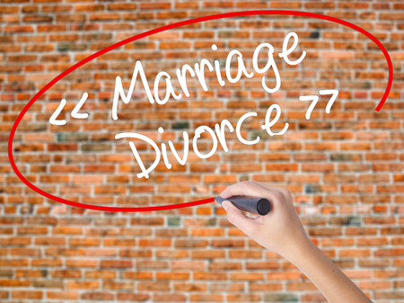 Woman Hand Writing Marriage - Divorce with black marker on visual screen. Isolated on bricks. Business concept. Stock Photo