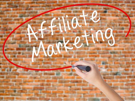 Woman Hand Writing Affiliate Marketing with black marker on visual screen. Isolated on bricks. Business concept. Stock Photo