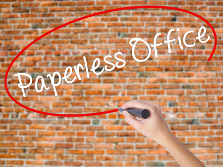 paperless: Woman Hand Writing Paperless Office  with black marker on visual screen. Isolated on bricks. Business concept. Stock Photo
