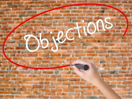 objections: Woman Hand Writing Objections  with black marker on visual screen. Isolated on bricks. Business concept. Stock Photo