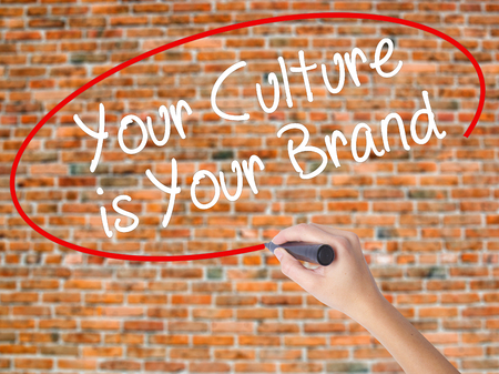 availability: Woman Hand Writing Your Culture is Your Brand with black marker on visual screen. Isolated on bricks. Business concept. Stock Photo