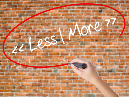 Woman Hand Writing Less - More with black marker on visual screen. Isolated on bricks. Business concept. Stock Photo