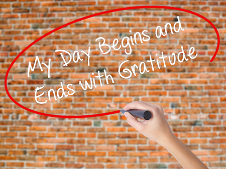 Woman Hand Writing My Day Begins and Ends with Gratitude with black marker on visual screen. Isolated on bricks. Business concept. Stock Photo
