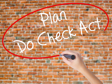 Woman Hand Writing Plan Do Check Act  with black marker on visual screen. Isolated on bricks. Business concept. Stock Photo