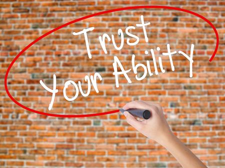 Woman Hand Writing Trust Your Ability  with black marker on visual screen. Isolated on bricks. Business concept. Stock Photo