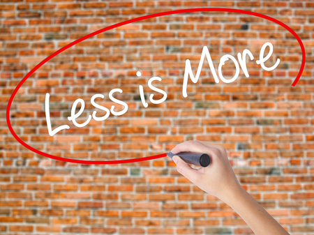 work less: Woman Hand Writing Less is More with black marker on visual screen. Isolated on bricks. Business concept. Stock Photo