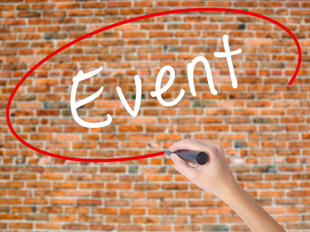 Woman Hand Writing Event with black marker on visual screen. Isolated on bricks. Business concept. Stock Photo Stock Photo