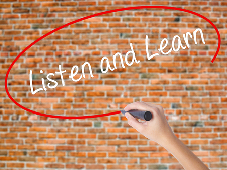 Woman Hand Writing Listen and Learn with black marker on visual screen. Isolated on bricks. Business concept. Stock Photo