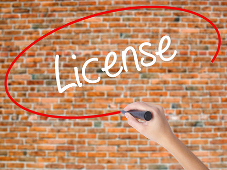 drivers license: Woman Hand Writing License with black marker on visual screen. Isolated on bricks. Business concept. Stock Photo