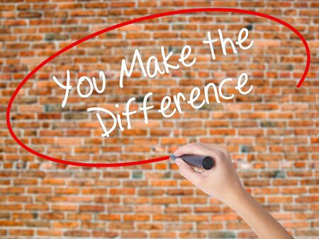 Woman Hand Writing You Make the Difference with black marker on visual screen. Isolated on bricks. Business concept. Stock Photo
