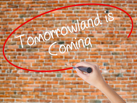 Woman Hand Writing Tomorrowland is Coming with black marker on visual screen. Isolated on bricks. Business concept. Stock Photo Stock Photo